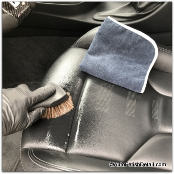 cleaning black car leather with horse hair brush